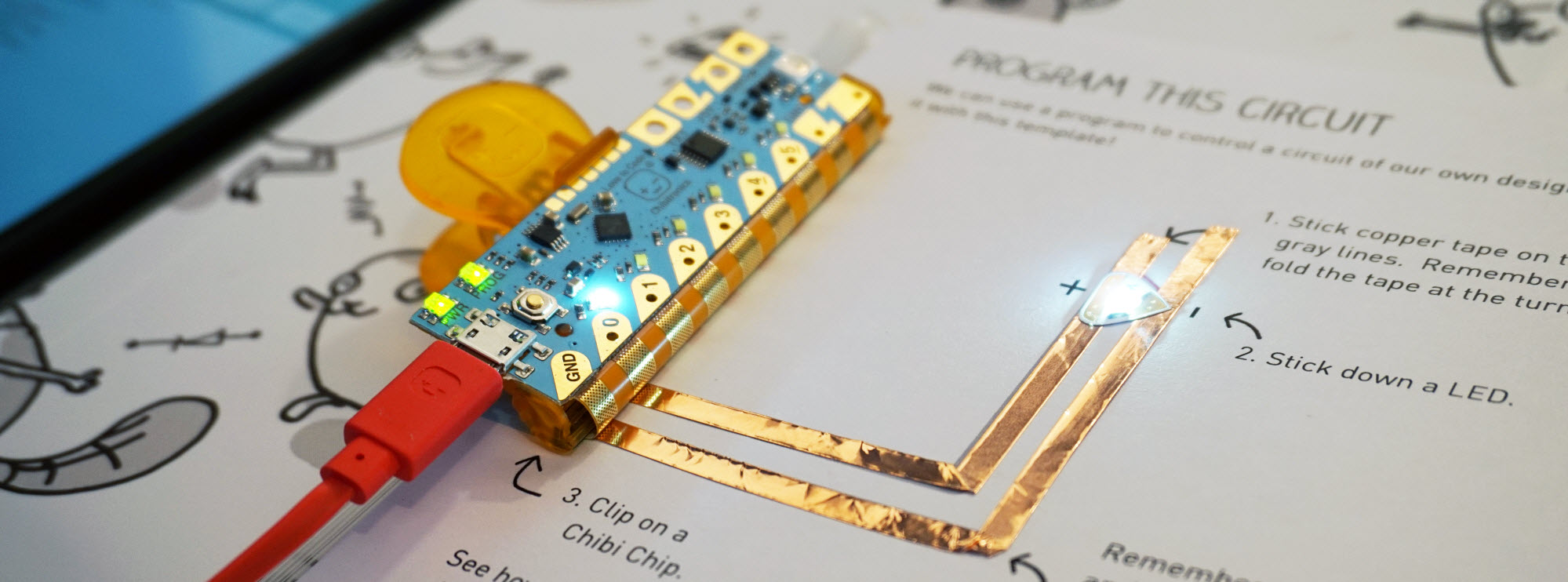 Chibi Chip clipped to a page, lighting an LED